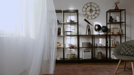 Video of a white curtain moving in a dark living room interior with a shelf, telescope, globe and armchair