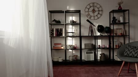 Video of a curtain moved by wind in a creative living room interior with a bookshelf and decorations Stok Video