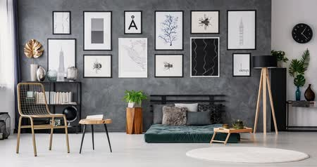 Stop-motion sequence of bedroom interior design. Video of cushions on green mattress and metal bedside table against gray, concrete wall. Stok Video