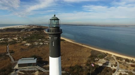 navigasyon : Aerial View of a Lighthouse and Shoreline Close Up on a Sunny Winter Day as Seen by a Drone Stok Video