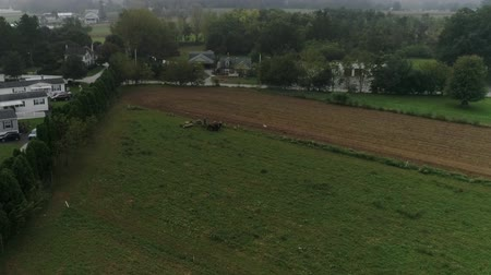 Пенсильвания : Drone Aerial View of Amish Farm Lands and Amish Farmer Harvesting in Fog Стоковые видеозаписи