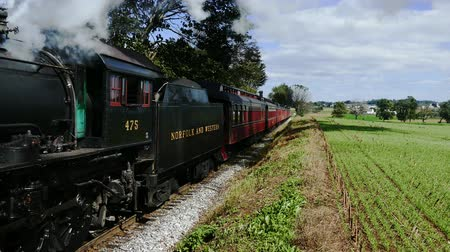puffing : Steam Passenger Train Puffing Along Amish Farm lands and Countryside Stock Footage