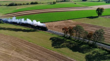 puffing : Steam Passenger Train Puffing Smoke Along Amish Countryside as Seen by a Drone