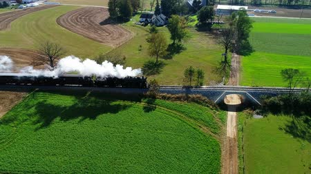 antiquado : Steam Passenger Train Puffing Smoke Along Amish Countryside as Seen by a Drone