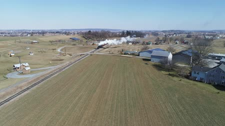 seyahat : Aerial View of Amish Countryside With Steam Passenger Train Puffing Through on a Winter Day as Seen by a Drone Stok Video