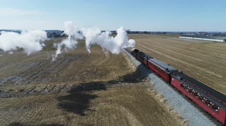 Aerial View of Amish Countryside With Steam Passenger Train Puffing Through on a Winter Day as Seen by a Drone Wideo