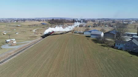 antiquado : Strasburg, Pennsylvania, February 2019 - Aerial View of Amish Countryside With Steam Passenger Train Puffing Through on a Winter Day as Seen by a Drone