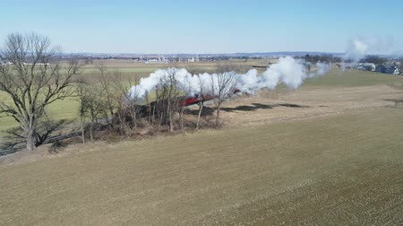 Пенсильвания : Strasburg, Pennsylvania, February 2019 - Aerial View of Amish Countryside With Steam Passenger Train Puffing Through on a Winter Day as Seen by a Drone