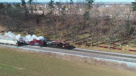 Пенсильвания : Strasburg, Pennsylvania, February 2019 - Aerial View of a Steam Freight and Passenger Combo Train as Seen by a Drone on a Sunny Winter Day
