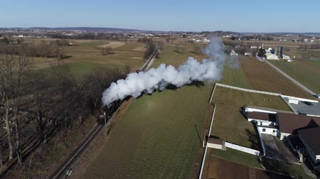 puffing : Strasburg, Pennsylvania, February 2019 - Aerial View of a Steam Freight and Passenger Combo Train as Seen by a Drone on a Sunny Winter Day