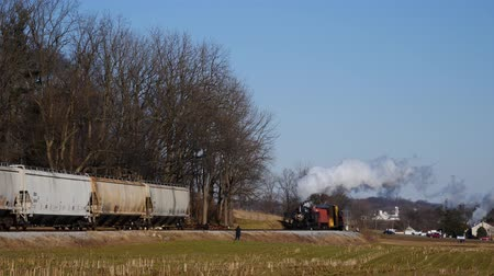 puffing : Strasburg, Pennsylvania, February 2019 - Steam Freight and Passenger Combo Train on a Sunny Winter Day Stock Footage