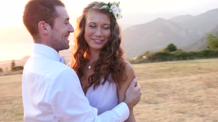 festividades : the bride and groom posing on the sunset with a wedding bouquet Stock Footage