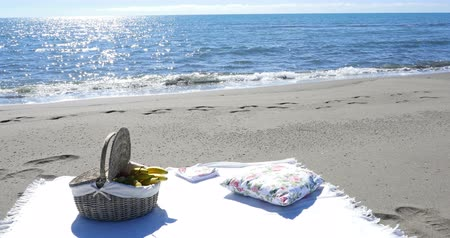 пикник : a fruit basket and a blanket for a picnic on the sandy beach near the sea