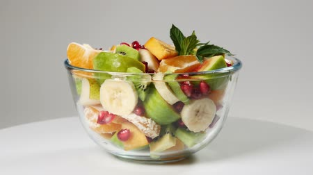 nektarinka : A fruit salad with mandarin, oranges, kiwi, pomegranate seeds, figs, banana and peaches