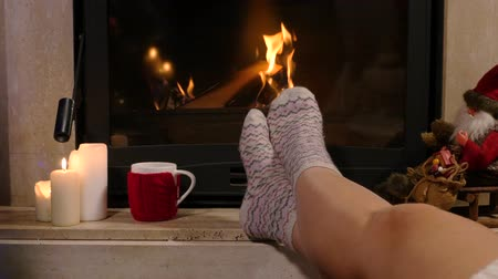 sock : Woman is sitting with cup of hot drink and book near the fireplace Stock Footage