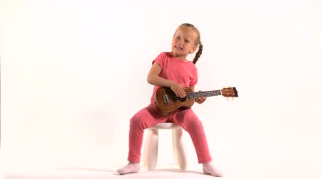 posando : little girl in purple dress playing the ukulele and sings Stock Footage