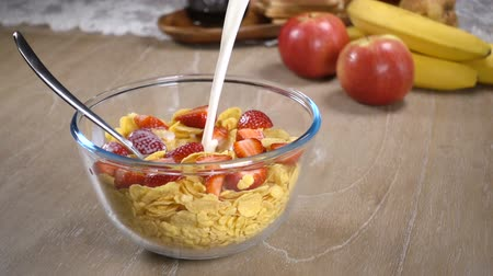cereais : Milk is poured into a bowl of cornflakes and strawberries Vídeos
