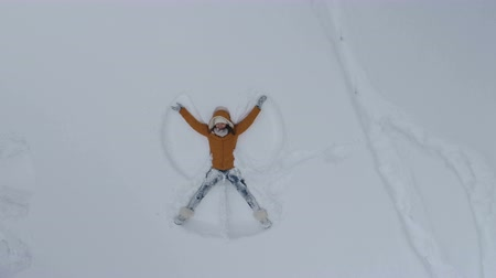 snow angel : Young woman making snow angels Stock Footage