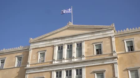greek flag : waving flag on the Greek parliament building in Athens, Greece