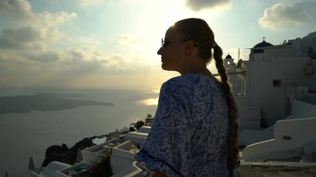 Киклады : Happy woman in white and blue dress enjoying her holidays on Santorini, Greece. View on Caldera and Aegean sea from Imerovigli. Active, travel, tourist concepts