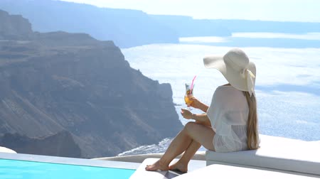 velkolepý : young woman drinking a cocktail enjoying a magnificent view of Santorini near the pool