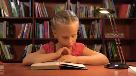 education kids : six year old girl reading sitting at the table by the light of a desk lamp