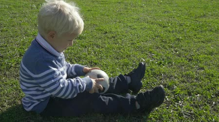 gramado : three year old boy sitting on the green grass on a sunny day with a soccer ball Stock Footage