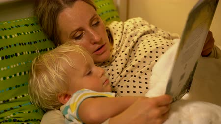racconto : mother and baby son reading a book in bed Filmati Stock