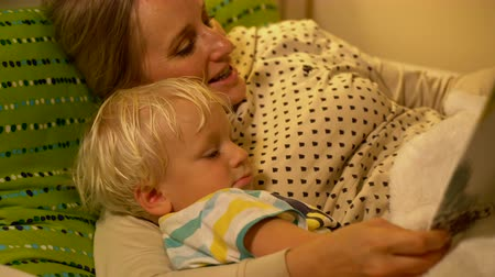 stories : mother and baby son reading a book in bed Stock Footage