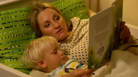 сказка : mother and baby son reading a book in bed Стоковые видеозаписи