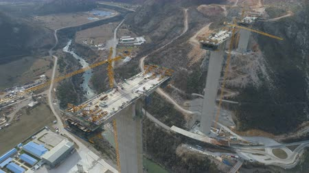 construction crane : Construction of bridge of a new highway through the Moraca canyon in Montenegro Stock Footage