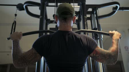 leunen : man in de sportschool traint de latissimus dorsi door de lat pulldown machine