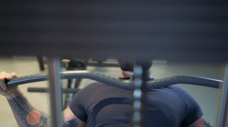 leunen : man in the gym trains the latissimus dorsi by the lat pulldown machine