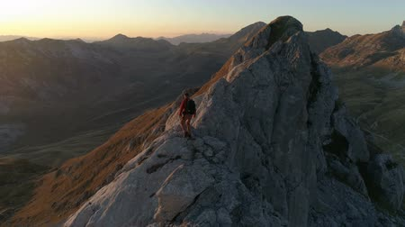 Aerial epic shot of a man hiking on the edge of the mountain in beautiful sunset Dostupné videozáznamy