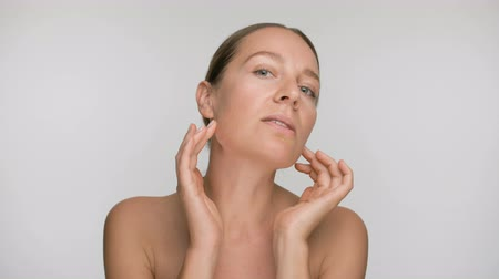 tilt : Close-up beauty portrait of young woman with smooth healthy skin, she gently touches her face with her fingers on white background Stock Footage
