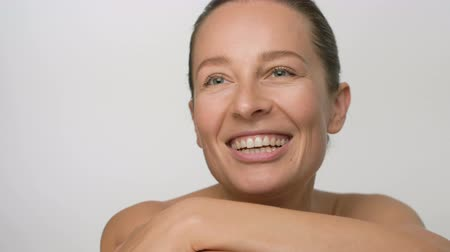Close-up beauty portrait of young woman with smooth healthy skin, she laughing at the camera