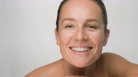 Close-up beauty portrait of young woman with smooth healthy skin, she gently touches her face with her fingers on white background and smiles