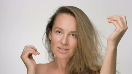 hydratace : Close-up beauty portrait of young woman with smooth healthy skin, she gently touches hair with her hands and playfully looks at the camera on white background Dostupné videozáznamy