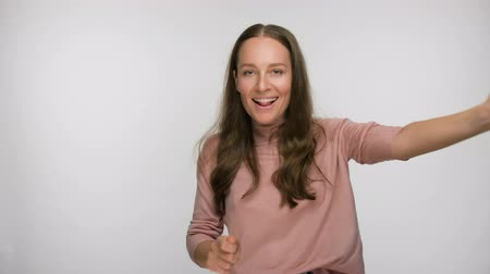 long hair : Happy carefree smiling brunette woman in pink blouse dancing over white background Stock Footage