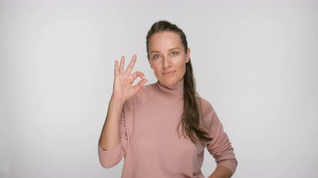 jest : Happy brunette woman showing ok gesture looking at the camera and smile over white background