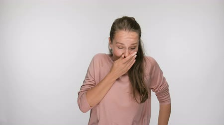 tosse : Portrait of sick woman sneezing in studio. Stock Footage
