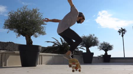 bruslení : Close up of skater skateboarder man doing ollie trick in slow motion, jump while riding