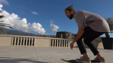 bruslení : Close up of skater skateboarder man doing ollie trick in slow motion, jump over the steps