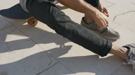 bruslení : a young male skateboarder ties a lace and then leaves on a skateboard