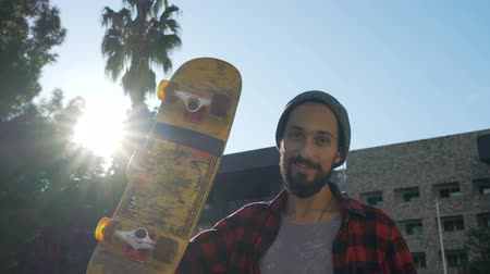 kickflip : portrait of a smiling skateboarder with a beard who carries a skate on his shoulder