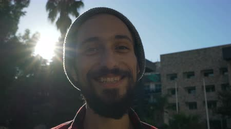 skateboard deck : portrait of a young man with a beard in a hat who is smiling while looking at the camera Stock Footage
