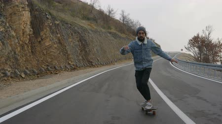 juventude : young man with a beard riding skateboard cruising downhill on countryside road