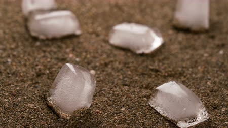resfriar : ice cubes are melting into sand leaving an imprints Vídeos