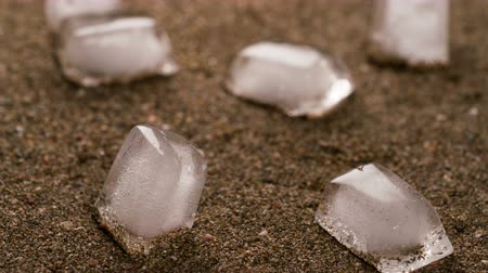 água salgada : ice cubes are melting into sand leaving an imprints Stock Footage