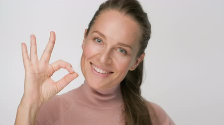 позирует : Happy brunette woman showing ok gesture looking at the camera and smile over white background
